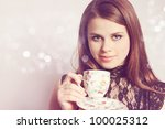 Young woman holds cup with the tea - stock photo