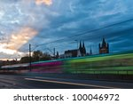 city view with a tram in motion blur and a moody evening sky in Cologne City in Western Germany with the famous Cologne Cathedral in the farther background - stock photo