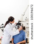 Female optometrist performing eye checkup with phoropter at clinic - stock photo