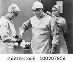 Women preparing doctor for surgery - stock photo