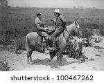 Cowboy and businessman playing checkers on horseback - stock photo