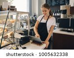 Stock photo portrait of young caucasian female woman cashier seller using touch pad for accepting client 1005632338