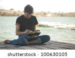 young boy reading on a pier | Shutterstock . vector #100630105