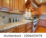 Stock photo gourmet kitchen boasts a curved kitchen hood over a subway tiled backsplash granite countertops 1006653478
