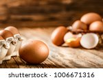Small photo of Brown eggs in carton box. Broken egg with yolk in background.