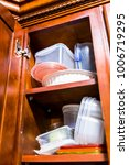 Stock photo open wooden kitchen cabinet door cupboard with many plastic containers dishes boxes lids 1006719295