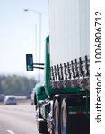 Small photo of Day cab green big rig semi truck for local deliveries of commercial cargo with tent covered semi trailer driving on the straight wide multiline road in sunshine weather