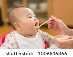baby eating a weaning food | Shutterstock . vector #1006816366