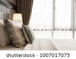 Stock photo comfort pillow on bed with light lamp decoration in hotel bedroom interior 1007017075