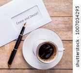 Small photo of Cease and desist letter on the table. Mug with spilled coffee. The concept is to stop the previous actions.