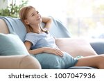 cute girl resting on couch with ... | Shutterstock . vector #1007047936