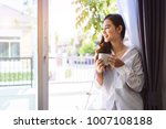 asian woman drinking coffee in... | Shutterstock . vector #1007108188