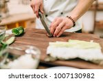 male cook making sushi rolls on ... | Shutterstock . vector #1007130982