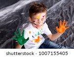 happy cute boy colors his hands.... | Shutterstock . vector #1007155405