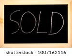 Blackboard with sold written on in white chalk - stock photo