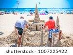 Two Adult Men Build A Sand...