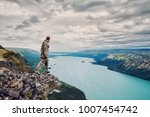 man is standing on cliff ... | Shutterstock . vector #1007454742