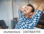 relaxed handsome man sitting at ... | Shutterstock . vector #1007864755