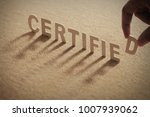 Small photo of CERTIFIED wood word on compressed or corkboard with human's finger at D letter.
