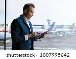 man looking at tablet while... | Shutterstock . vector #1007995642