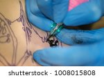 Small photo of Selective focus.Professional tattoo artist at work.Needle tattoo machines inject a black ink into the skin of a man.Tattoo art on body.Makes a tattoo.Professional tattooist working tattooing in studio
