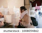 girl looks at storefront   Shutterstock . vector #1008054862