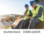 Small photo of Couple of workers taking a break in their job and looking telephone on steamroller bulldozer
