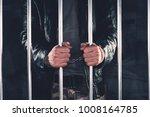 handcuffed man behind prison... | Shutterstock . vector #1008164785