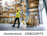 male warehouse worker pulling a ... | Shutterstock . vector #1008220975
