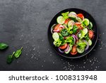 Healthy vegetable salad of fresh tomato, cucumber, onion, spinach, lettuce and sesame on plate. Diet menu. Top view.