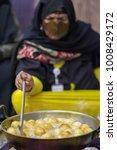 emirate lady cooking luqaimat... | Shutterstock . vector #1008429172