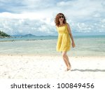 Asian Women happy on the Beach with vibrant yellow dress - stock photo