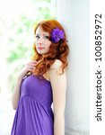 Young beautiful redhead woman portrait with flower in her hair. Outdoor. - stock photo