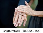 Small photo of Older couple displaying their wedding rings after getting married. Their hands show the beauty of time, and set forth the idea that you are never too old for love or marriage.