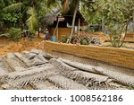 Small photo of BELUMMAHARA, SRI LANKA, FEBRUARY 5, 2012. Men toil at producing mud bricks in front of his home in the countryside.