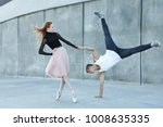A young couple in love passionately dances on a city street. Dancer and sportsman Parkour. Balance and stunts in the dance. Meshenie classical and modern dance. - stock photo