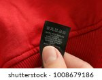 Small photo of Woman reading instruction on clothing label, closeup