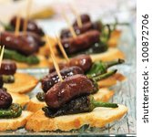 closeup of a plate with spanish pinchos made with chorizos an Padron peppers - stock photo