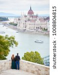 Elegant pair is enjoying each other on the background of Danube River and Parliament Building in Budapest, Hungary. Blurred background
