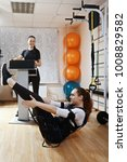 Small photo of Caucasian woman makes abdominal muscles exercises in gym. Female trainer standing aside manages electric muscle stimulation purposed to increase effectiveness of training. Vertical shot