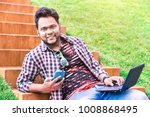 cheerful indian young man using ... | Shutterstock . vector #1008868495