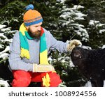 Small photo of Guy with firtrees covered with snow on background, defocused. Friendship and allegiance concept. Man wears knitted hat, scarf and gloves with black dog. Macho with beard and mustache pats dog.