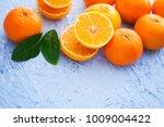 fresh tangerines on blue...   Shutterstock . vector #1009004422