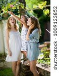 three girls in the green garden | Shutterstock . vector #1009123852