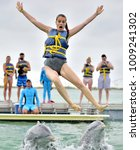 dolphins toss the girl up out... | Shutterstock . vector #1009241302