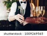 waiter brings glasses of... | Shutterstock . vector #1009269565
