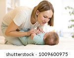 a pretty woman plays with a baby | Shutterstock . vector #1009600975
