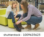 mom chooses winter shoes for... | Shutterstock . vector #1009635625