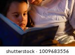 caring father is reading a book ... | Shutterstock . vector #1009683556
