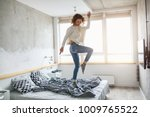 young happy woman jumping on... | Shutterstock . vector #1009765522
